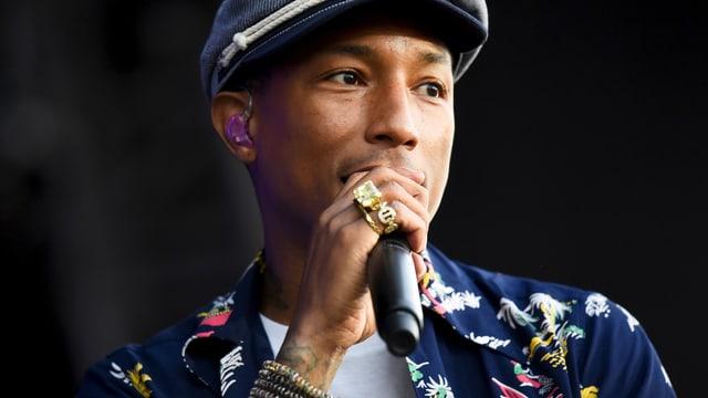 Pharrell Williams mit Hawaihemd und Schiebermütze.