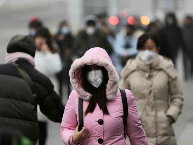 Menschen in Peking mit Mundschutz.