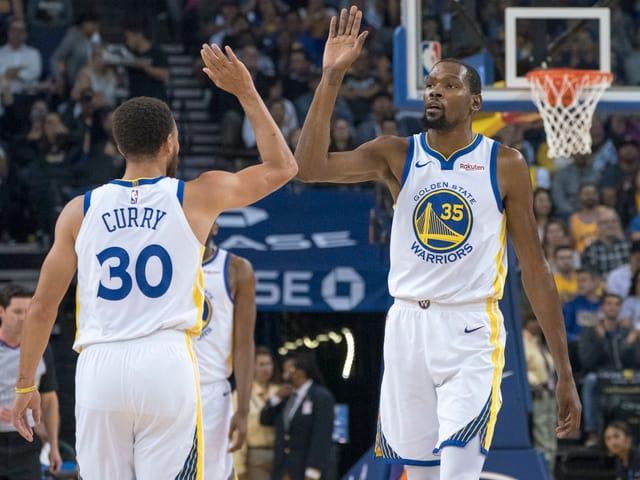 Stephen Curry (links) und Kevin Durant von den Golden State Warriors klatschen sich ab