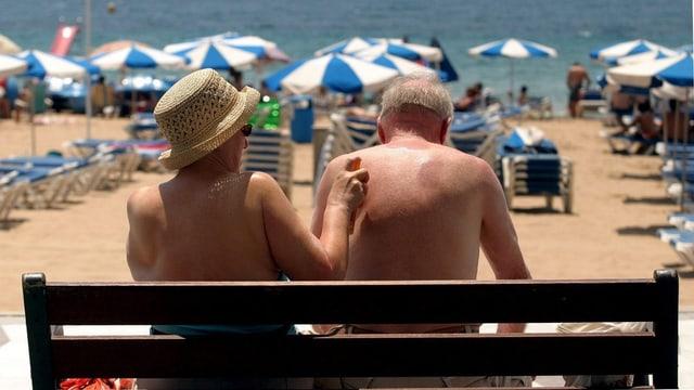 Eine Seniorin tippt mit dem Finger auf die Haut ihres Ehemanns, um einen Fleck zu zeigen.
