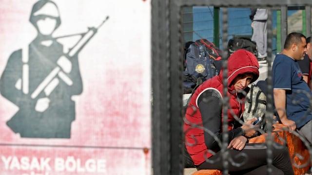 Flüchtlinge warten im türkischen Dikili hinter Gittern auf den Transport in ein Flüchtlingscamp.