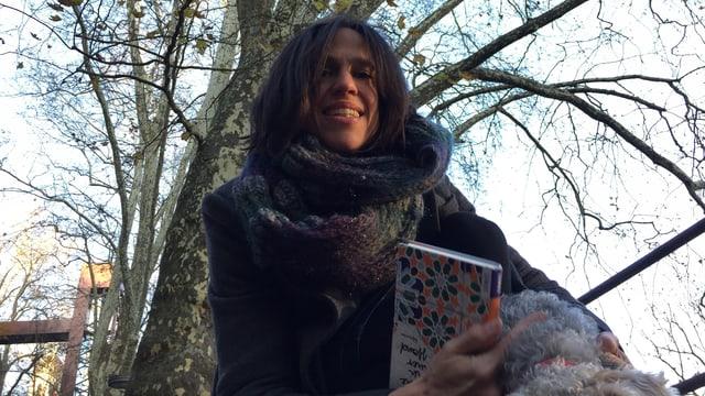 Annette König geht alleine mit ihrem Lakeland Terrier spazieren.  Das Buch von Kaouther Adimi «Steine in meiner Hand» hat sie dabei