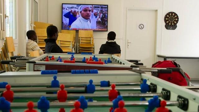 Symbolbild: Asylbewerber sitzen in einer Unterkunft vor einem Fernseher, im Vordergrund ein «Töggeli-Kasten».