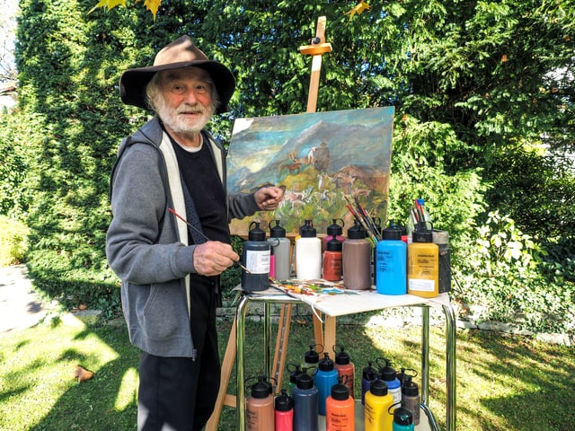 Ernst Sieber steht vor einer Staffelei im Grünen, darauf ein Landschaftsbild.