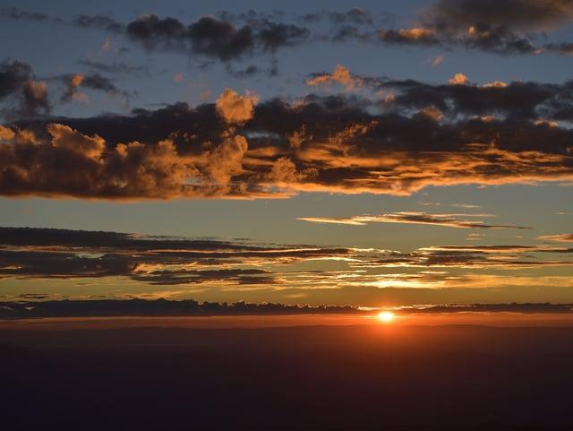 Feuerrot geht die Sonne am Horizont unter. Die Wolkenfelder werden in ein warmes, rötliches Licht getaucht.