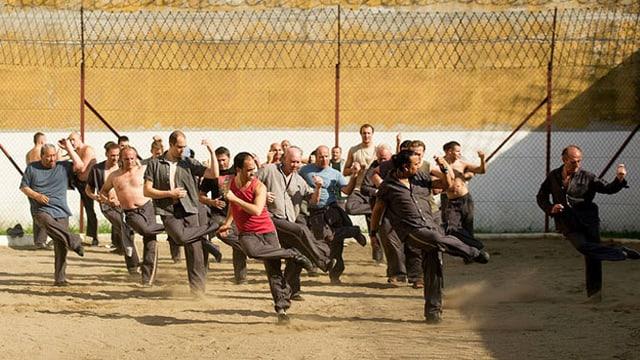 Gefängnisinsassen beim Tanz im Gefängnishof.