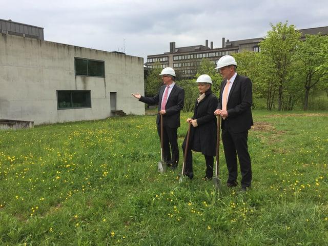 Kantonsbaumeister Matthias Haag, Justizdirektor Jacqueline Fehr und Staatsarchivar Beat Gnädinger stehen mit Schaufeln auf einer Wiese.