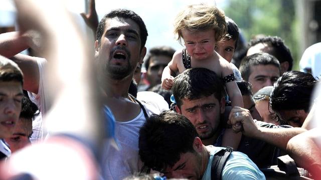Eine Menschenmenge von Flüchtenden an der Grenze zwischen Mazedonien und Serbien. Ein kleines Mädchen sitzt auf den Schultern eines zerknirscht dreinschauenden Mannes und weint.