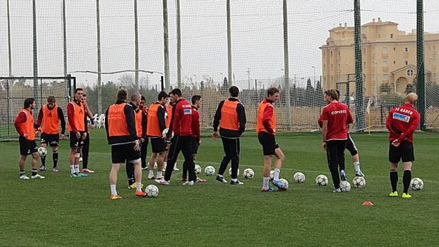 Die Mannschaft auf einem Fussballfeld im Training, im Hintergrund eine spanische Hotelanlage.