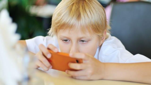 Ein Bub sitzt an einem Tisch und spielt mit dem Smartphone.