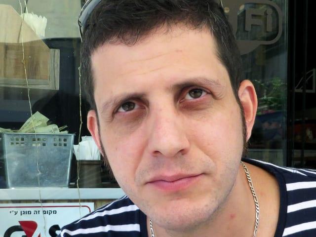 Ein Mann mit gestreiftem T-Shirt und Sonnenbrille im Haar, den Blick gegen oben gerichtet.