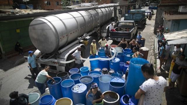 Einwohner von Caracas füllen Trinkwasser aus einem Tanklaster in grosse blaue Fässer.