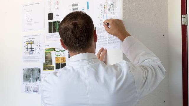 Collin Ewald an einer Wand mit wissenschaftlichen Grafiken