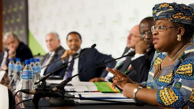 Frau in afrikanischer Kleidung spricht neben mehreren Herren in Anzügen