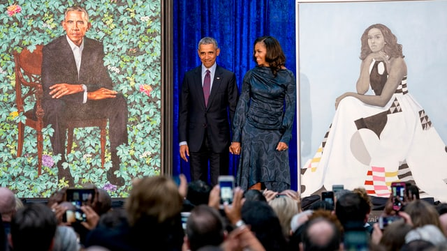Die Obama stehen neben den Porträts.