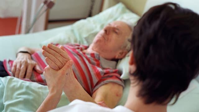 Eine Frau hält die Hand eines älteren Mannes, der in einem Spitalbett liegt.