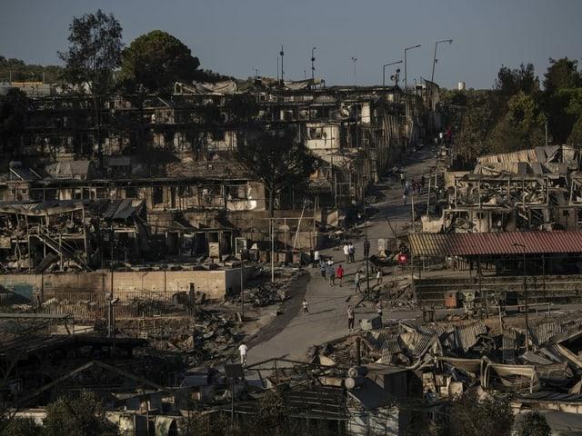 Ein Mann geht über die Trümmer des Flüchtlingscamps hinweg durch den Rauch.