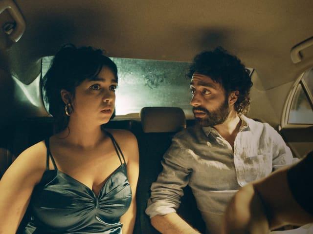 Eine junge Tunesierin sitzt im Auto hinten neben einem jungen Tunesier.