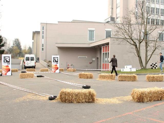 Zu sehen ist ein Parkplatzgelände. Es ist mit Strohballen und Absperrbänder zur Rennstrecke verwandelt worden. Auf Schildern liest man: SRF 3.