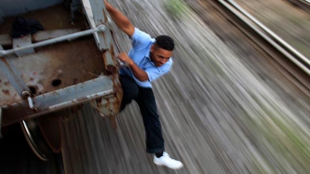 Ein Mann springt von einem fahrenden Zug.