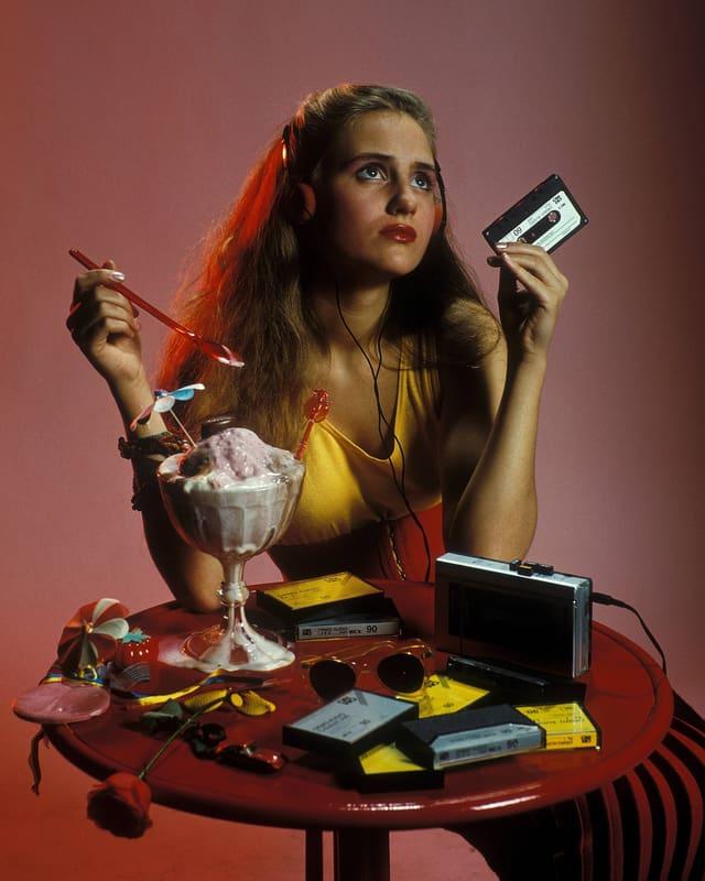 Eine Frau  löffelt ein Eis und hält in der anderen Hand eine Kassette.