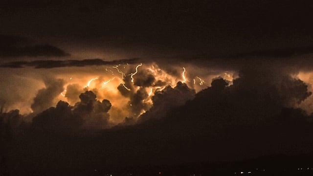 In der dunklen Nacht durch Blitze erhellte Cumulonimbus-Wolken