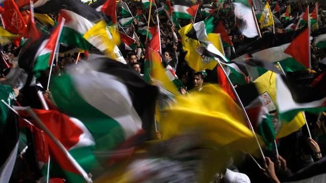 Palästinenser gehen in  Nablus auf die Strasse und schwingen Fahnen.