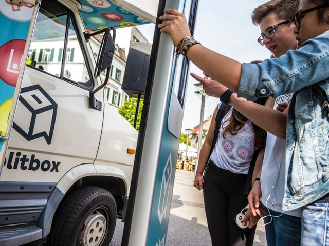 Jugendliche klicken auf einem grossen Smartphone vor dem politbox-Bus.