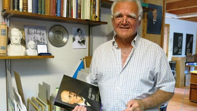 Res Marty steht mit seiner Joachim Raff Biografie vor seinem Archiv.