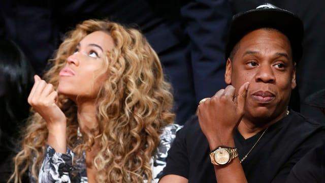 Sängerin Beyoncé starrt nach oben, daneben ihr Mann Jay-Z schaut etwas genervt in die andere Richtung.