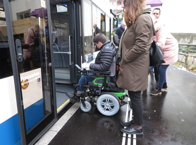 Eine behinderte Frau kann dank behindertengerechter Rampe mit dem elektrischen Rollstuhl in einen Bus.