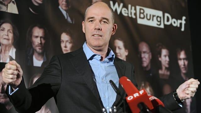 Matthias Hartmann steht mit geballten Fäusten auf einem Podium, vor ihm Mikrofone.