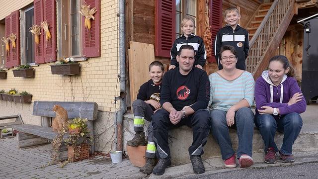 Familie sitzt vor einem Bauernhaus.