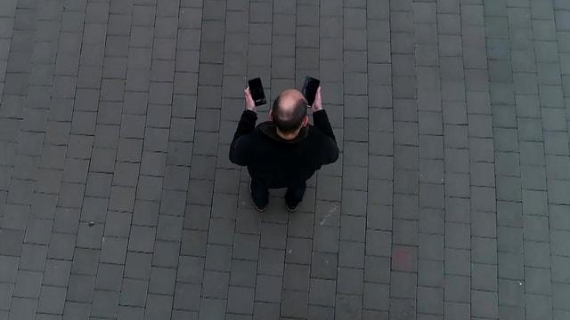 Digitalredaktor Reto Widmer von oben aufgenommen, zwei Smartphones in der Hand.