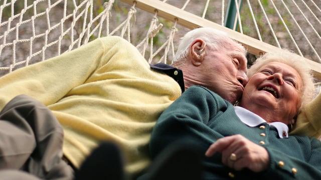 Ein älteres Paar liegt in einer Hängematte, wobei der Herr die lachenden Dame auf die Wange küsst.