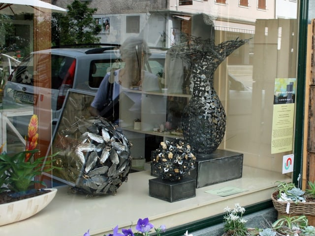 Stahlskulpuren mit Blumenmotiven stehen in einem Schaufenster.