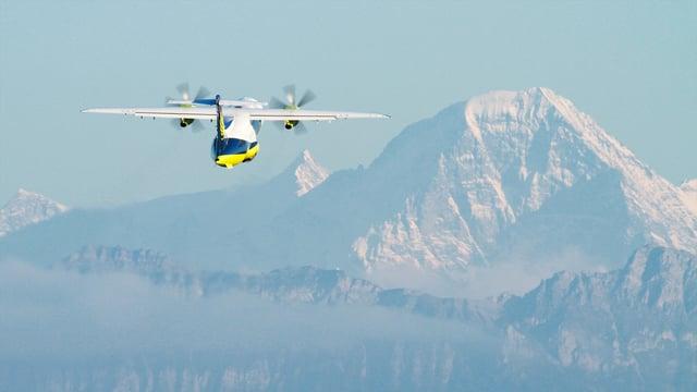 Flugzeug nach dem Start, im Hintergrund die Alpen.