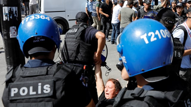 Polizisten schleifen eine Frau davon.