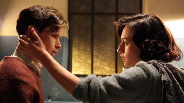 Eine Frau streicht einem jungen Mann durchs Haar.