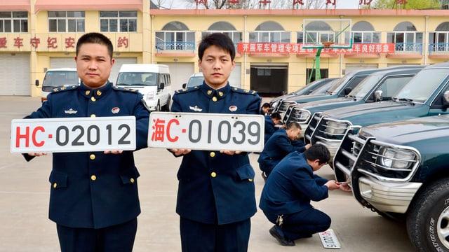Zwei chinesische Soldaten halen weisse Nummernschilder in den Händen. Im Hintergrund montieren Soldaten Nummernschilder an Autos.