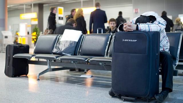 Sitzender Mann hat Kopf auf Koffer gelegt.