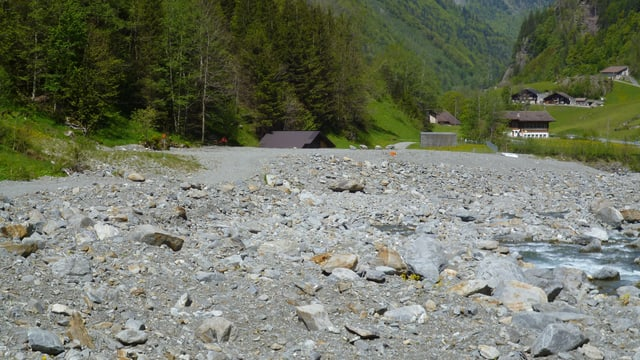 Bachbett mit kleinem Dorf im Hintergrund