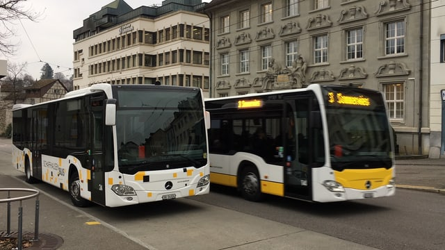 Ein Bus der RVSH an einer Bushaltestelle wird von einem Bus der VBSH überholt.