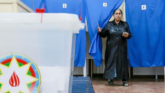Eine Frau läuft aus einem Wahllokal heraus