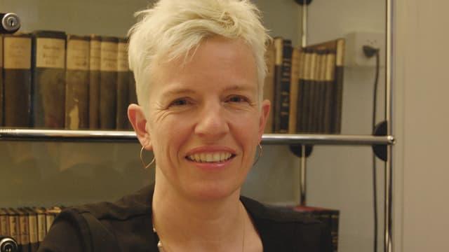 Eine Frau mit blondem, kurzem Haar steht vor einem Glasregal mit alten Büchern.