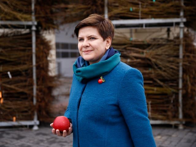 Die Politikerin Beata Szydlo hält einen Apfel in der Hand