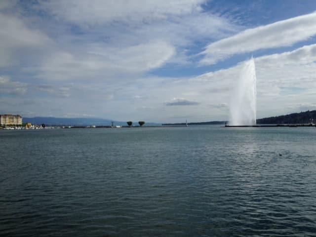 Der Genfer Jet d'eau, im Hintergrund die Stadt Genf.