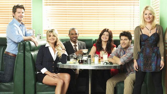 Sechs Protagonisten sitzen im Restaurant und posieren für Foto.