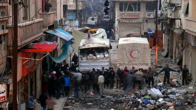 Lastwagen des Syrischen Roten Halbmonds, davor eine Menschenkette, um die Güter zu verteilen.