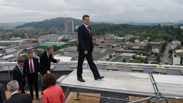 Regeirungsrat Rickenbacher bringt sich auf einem Hausdach fürs Regierungsfoto in Stellung.
